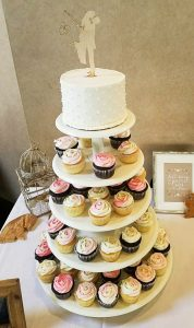 """Cupcake tower with a 6"""" round cutting cake on top."""